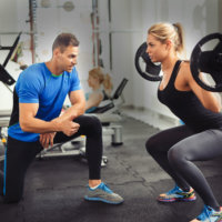 Woman does squat with trainer at gym